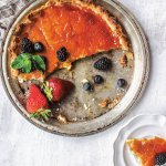 Buttermilk pie in a pie tin with berries