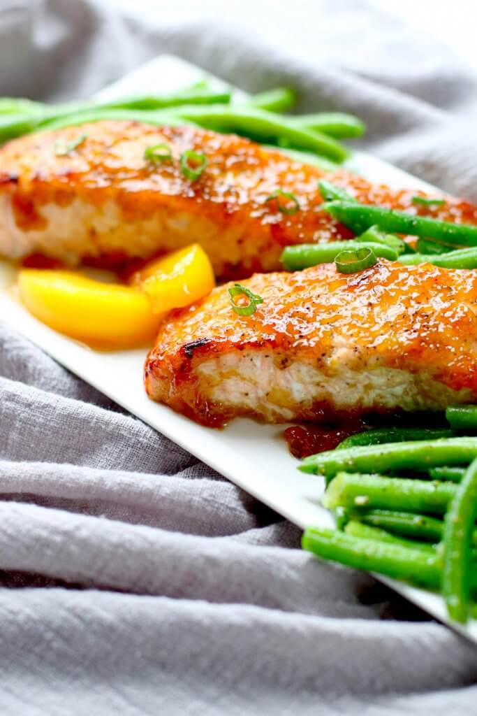 Two pieces of glazed salmon on a plate with green beans.