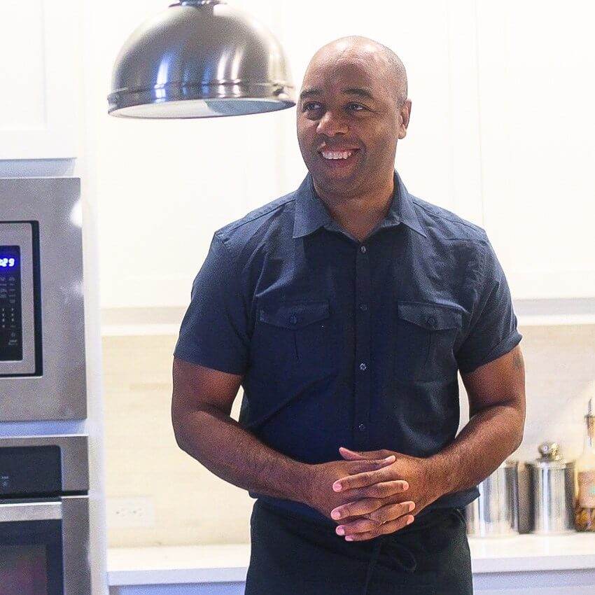 Marwin Brown wearing a navy shirt. He is a black man with his hands clasped standing in a kitchen.