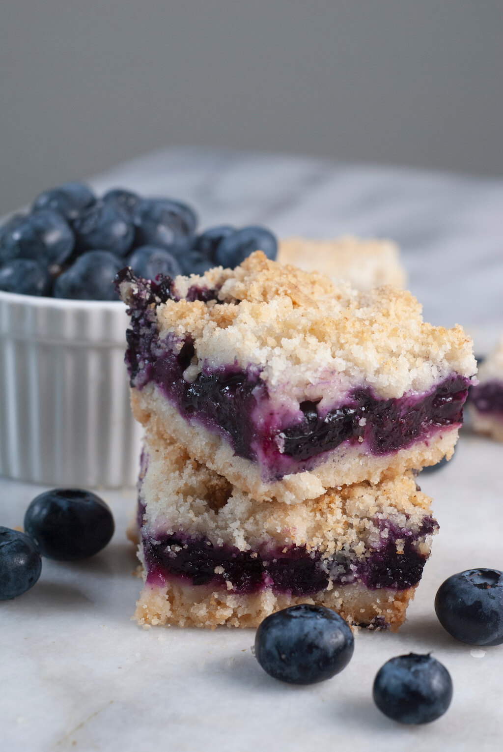 Two vegan blueberry squares stacked on a marble slab. There are blueberries in the background.